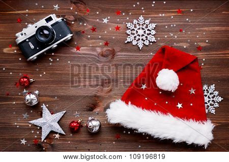 Christmas And New Year Background With Old Fashioned Camera, Red Santa's Hat, Christmas Decorations