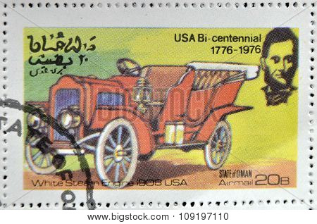 OMAN - CIRCA 1976: A stamp printed in State of Oman shows a american carwhite steam engine 1908 usa