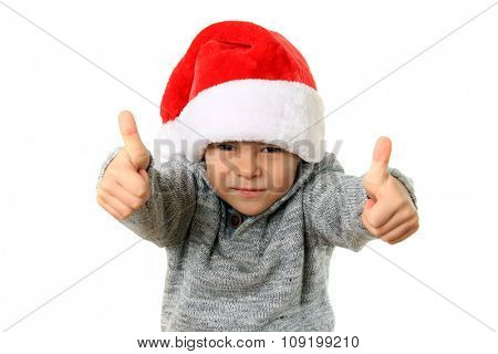 Five year old boy wearing a Santa hat with both thumbs up. Studio isolated.