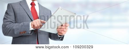 Hands of businessman with tablet computer over blue office background.