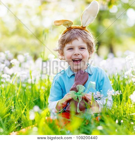 Little kid boy eating chocolate Easter bunny outdoors
