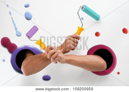 Male  hands through the holes on a white background  with colorful paint splotches are holding an yellow paint rollers