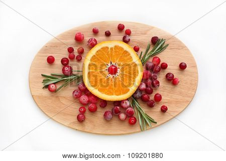 Cranberries, orange and rosemarya on the wooden board