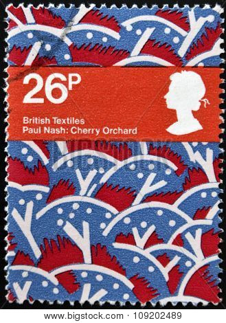 stamp printed in United Kingdom dedicated to british textiles shows Cherry Orchard by paul nash