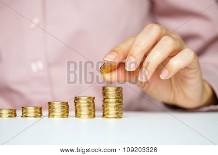 Female Hand Stacking Gold Coins Into Increasing Columns