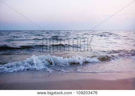 Sea wave on the shore at sunset