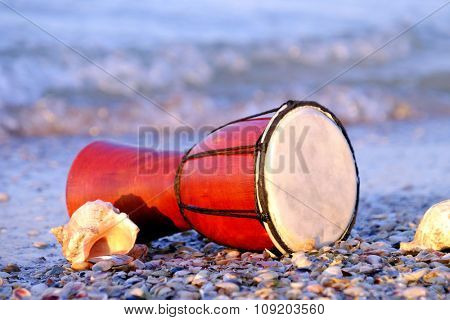 Beautiful ethnic drum with seashells on the beach on sunrise background