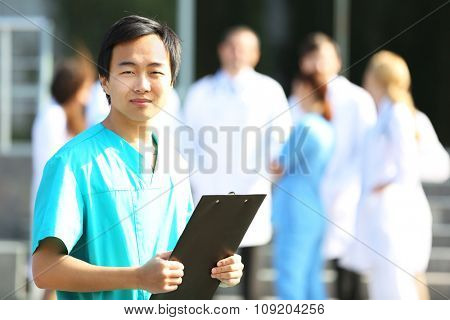 Young smiling doctor with clipboard in hands standing against group of medical workers