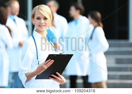Beautiful smart woman doctor with clipboard in hands standing against blurred group of medics