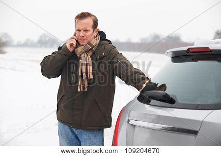 Motorist Broken Down In Snowy Landscape