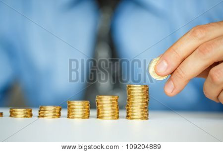Male Hand Stacking Gold Coins Into Increasing Columns