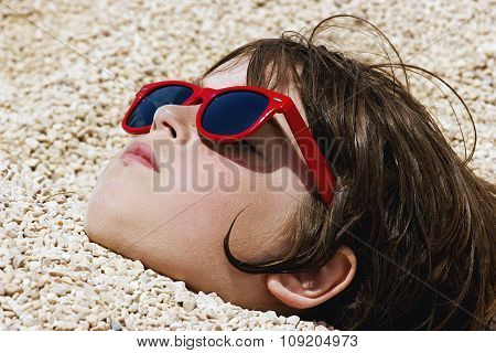 Boy Buried In The Pebbles On The Beach