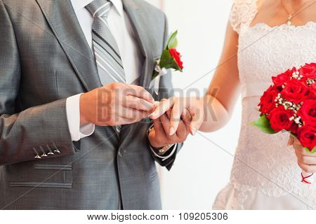 Groom wearing the ring to bride.