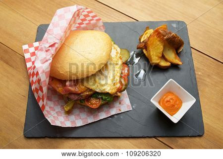 Beef burger with fried egg and chips.