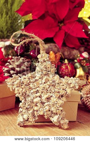 a star-shaped christmas  ornament on a rustic wooden surface with gifts and other christmas ornaments in the background