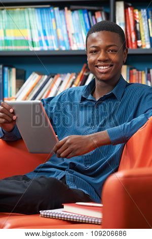Male Teenage Student Using Digital Tablet In Library