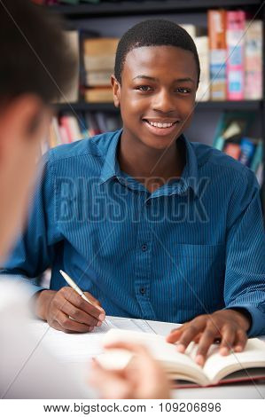 Male Teenage Student Working In Classroom