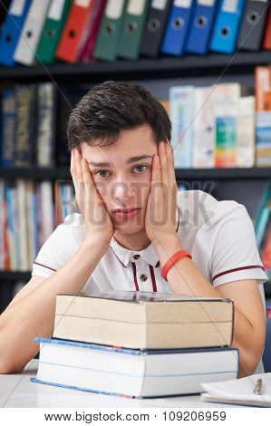 Stressed Male Pupil Working In Library