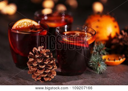 Mulled wine with spices and Christmas tree on dark wooden background