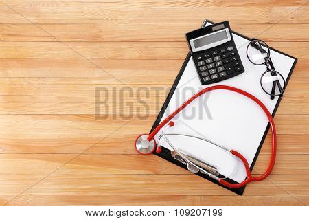 Medical stethoscope with clipboard on wooden table close up