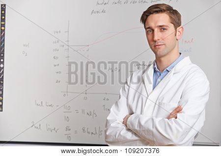 Portrait Of Science Teacher Standing In Front Of Whitebaord