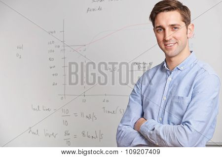 Portrait Of Teacher Standing In Front Of Whitebaord