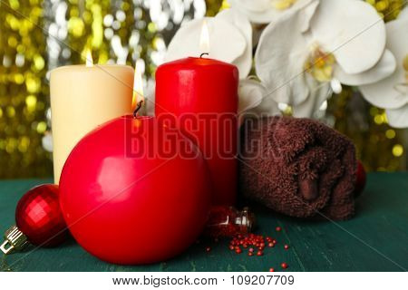 Composition of alight candles, towel and flower on green wooden table against sparkle background