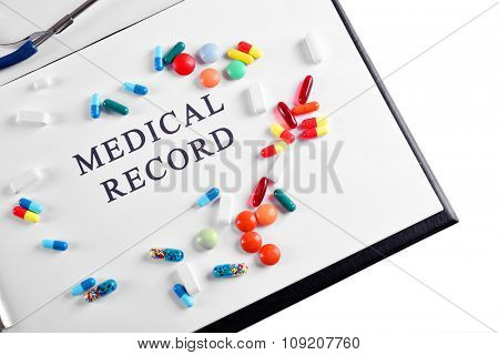 Medical record and pills close up