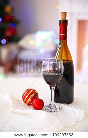 Bottle and glass of wine with Christmas decor against colorful bokeh lights background
