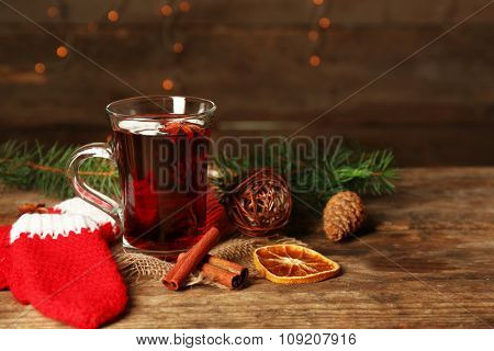 Christmas composition of mulled wine, cinnamon, pine and red knitted mittens on wooden table