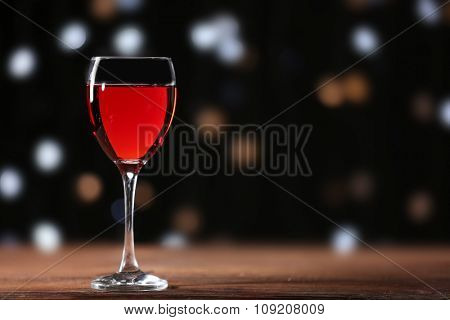 Wine glass on wooden table against defocused lights background