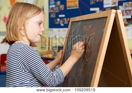 Young Girl Writing On Blackboard In School Classroom