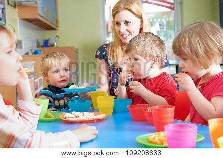 Teacher With Pre School Children Eating Healthy Snacks At Break time