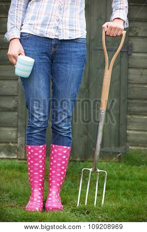 Woman In Pink Wellingtons Holding Garden Fork And Cup