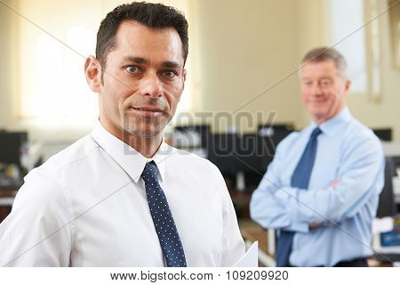 Young Businessman With Senior Mentor In Office
