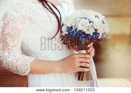 Bride in white dress holding wedding bouquet of blue flowers