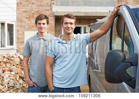 Two Builders Standing Next To Van