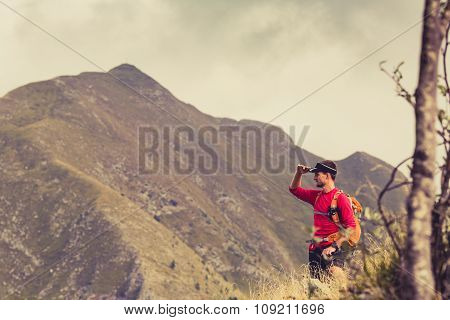 Hiking man backpacker climber or trail runner in mountains looking at beautiful inspirational view