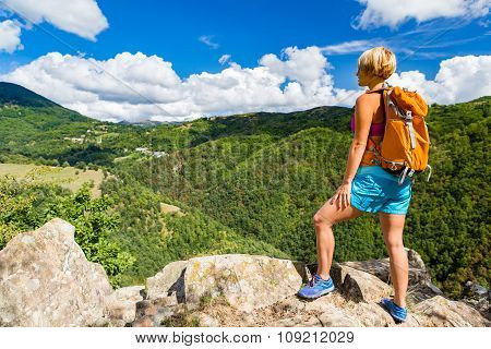 Hiking woman looking at inspirational mountains landscape. Fitness and healthy lifestyle outdoors