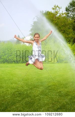 Girl jumps under spray drops