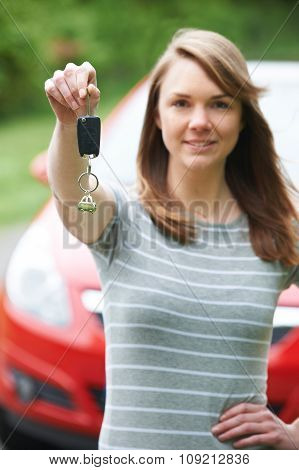 Young Female Driver Holding Car Keys In Front Of Vehicle