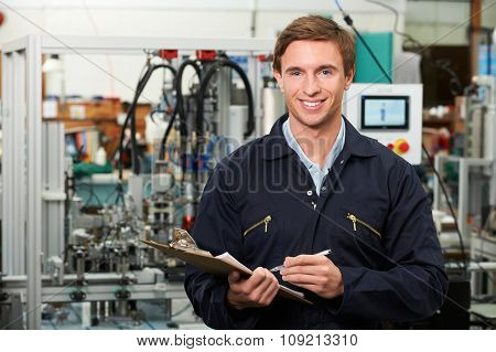 Engineer Holding Clipboard In Factory