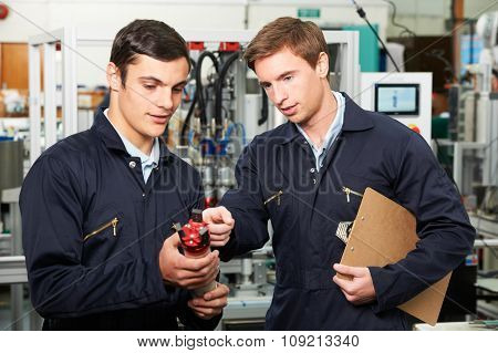 Engineer And Trainee Discussing Component In Factory