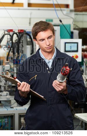 Engineer Inspecting Component In Factory