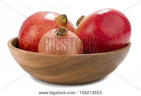 Pomegranates in wooden bowl isolated on white background.
