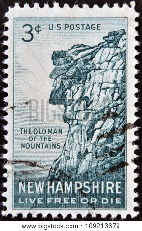 A stamp printed in USA shows Old man of the mountains New Hampshire Live Free or Die circa 1955