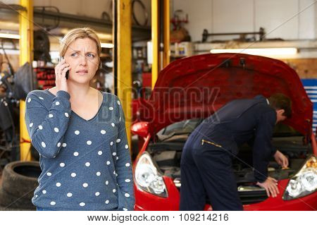 Worried Female Customer On Phone In Garage