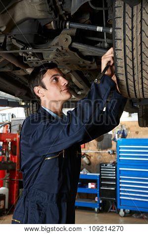 Trainee Mechanic Working Under Car