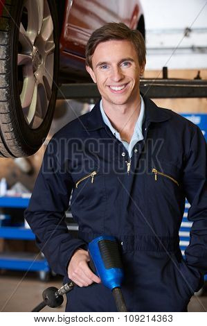 Portrait Of Mechanic In Garage With Air Hammer