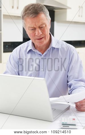 Concerned Senior Man Looking At Finances On Laptop